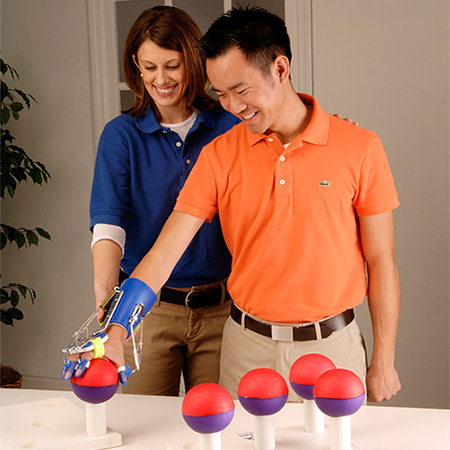 Man in orange shirt using the Saeboflex to pick up therapy balls