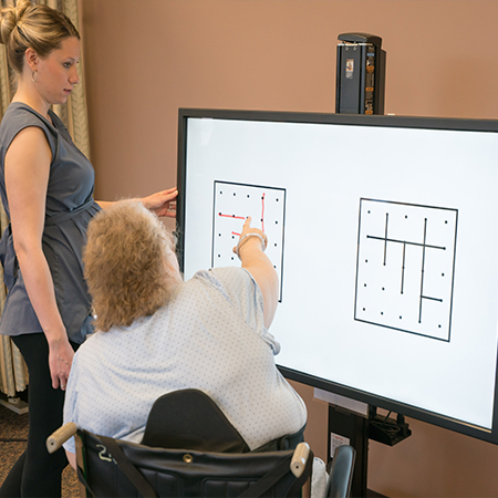 Woman touching the BITS screen while a therapists watches