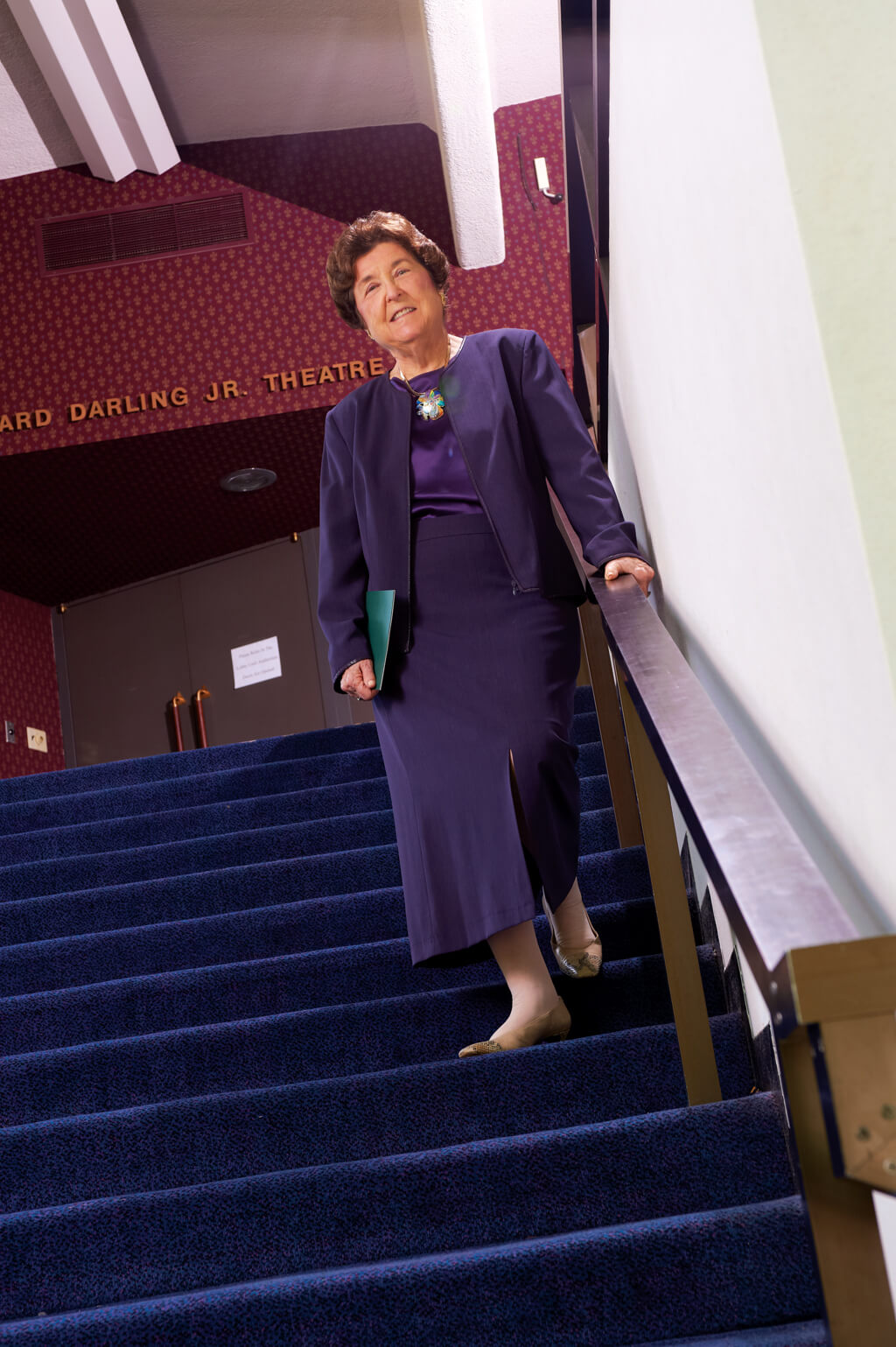 Esther standing in a purple dress on the stairs of the theater