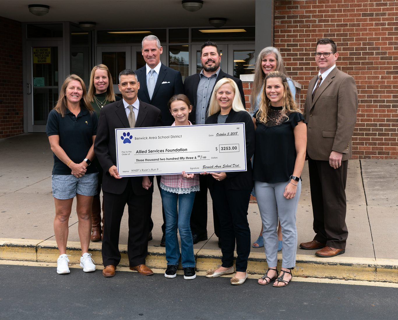 Berwick Area School District adults pose with large check with student