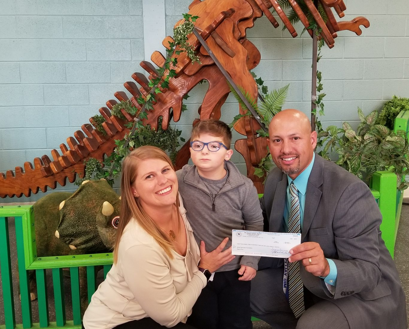 Child and adults pose with check in front of dinosaur display